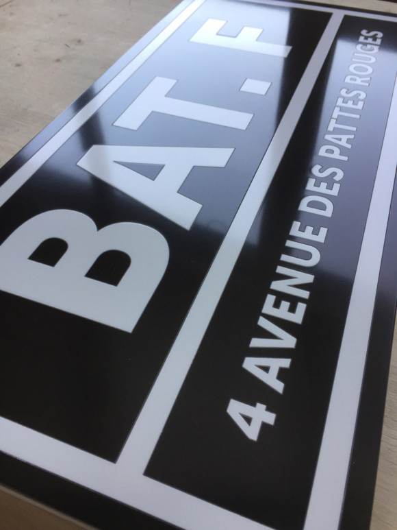 Signalétique intérieure en résine acrylique noire et blanche assemblée dans les règles de l'art de la marqueterie