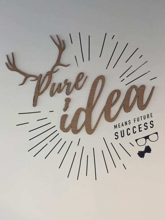 """Sticker mural décoratif """"Pure Idea""""en bois dans les bureaux de l'agence Pure Illusion"""